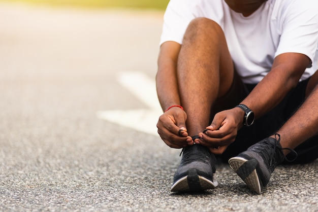 Corredor de esporte homem negro usar relógio sentado ele tentando sapatos cadarço Foto Premium