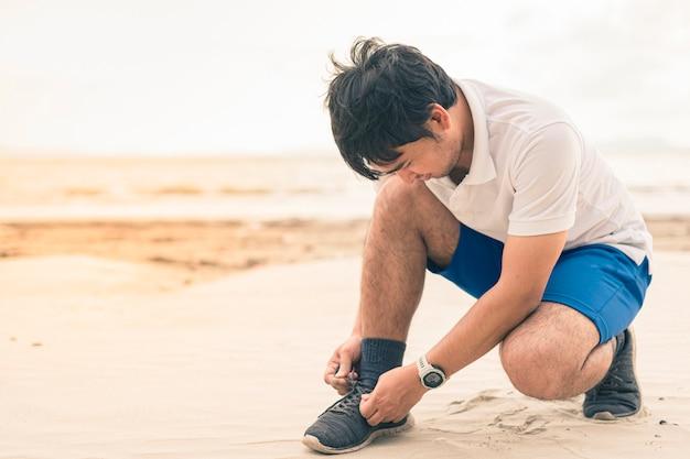Corredor de homem, amarrando o cadarço pronto para correr na praia Foto Premium