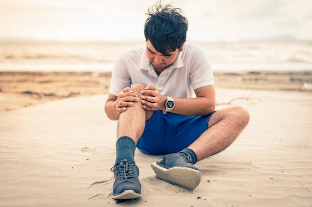 Corredor de homem segurar o joelho em dor no fundo da praia Foto Premium