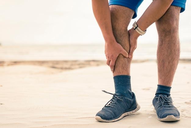 Corredor de homem segurar seus esportes feridos perna no fundo da praia Foto Premium