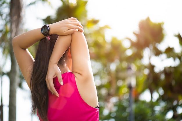 Corredor de mulher, esticando o braço no parque. Foto Premium