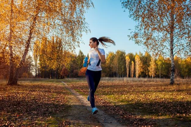 Corredor de treinamento no parque outono, mulher correndo com garrafa de água ao pôr do sol, estilo de vida ativo Foto Premium