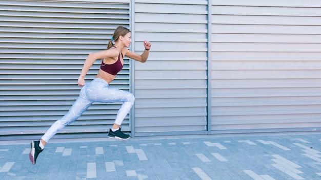 Corredor feminino saudável ativo, movimentando-se na frente do obturador Foto gratuita
