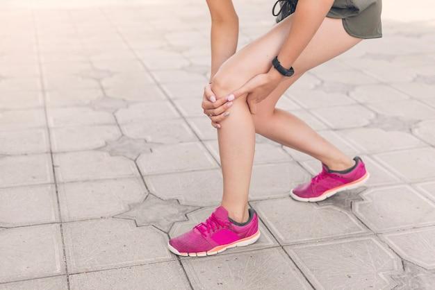 Corredor feminino, tendo, joelho, ferimento, ficar, ligado, pavimento Foto Premium
