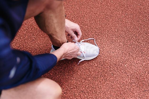 Corredor masculino amarrando o cadarço do sapato depois de correr ao longo da pista de corrida vermelha. Foto Premium