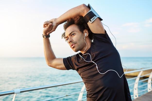 Corredor masculino de pele escura com belo corpo atlético e penteado espesso alongando os músculos, levantando os braços enquanto se aquece antes da sessão de treino matinal. Foto gratuita