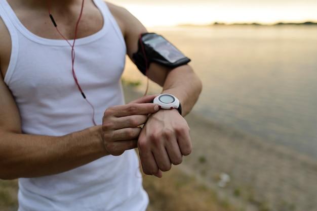 Corredor no parque usando relógio inteligente Foto Premium