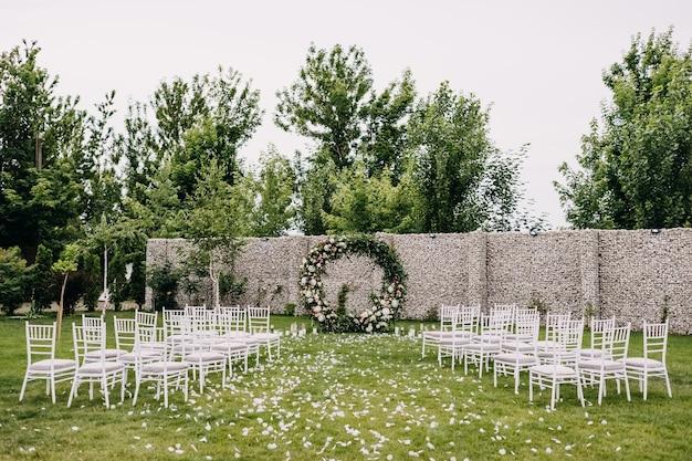 Corredor vazio para a cerimônia de casamento com cadeiras enfileiradas e um arco de flores Foto Premium