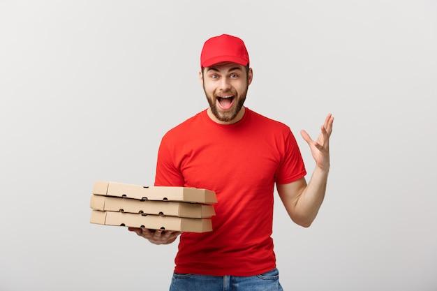 Correio bonito do homem de entrega da pizza no uniforme vermelho com o tampão que guarda caixas da pizza. Foto Premium