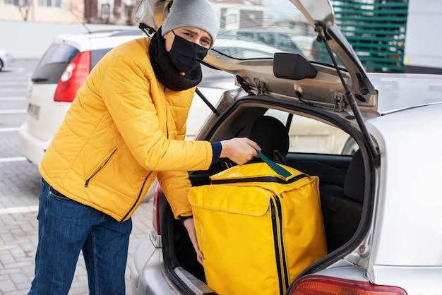Correio com máscara médica preta tirando mochila amarela do carro. serviço de entrega de comida Foto gratuita