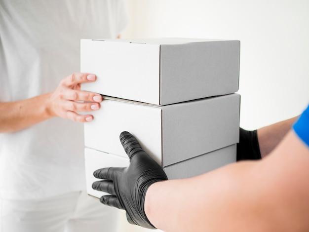 Correio de close-up com luvas entregando caixas Foto gratuita