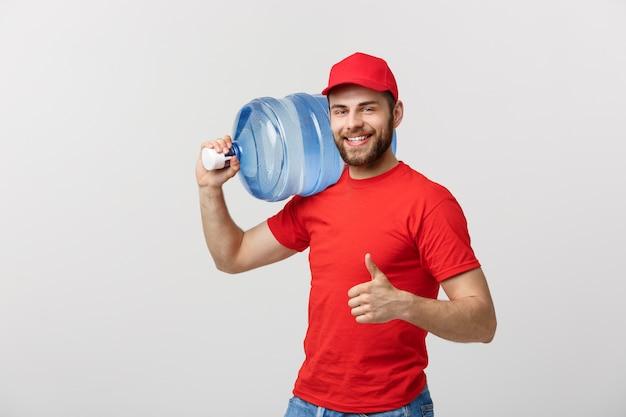 Correio de entrega de água engarrafada em t-shirt vermelha e boné Foto Premium