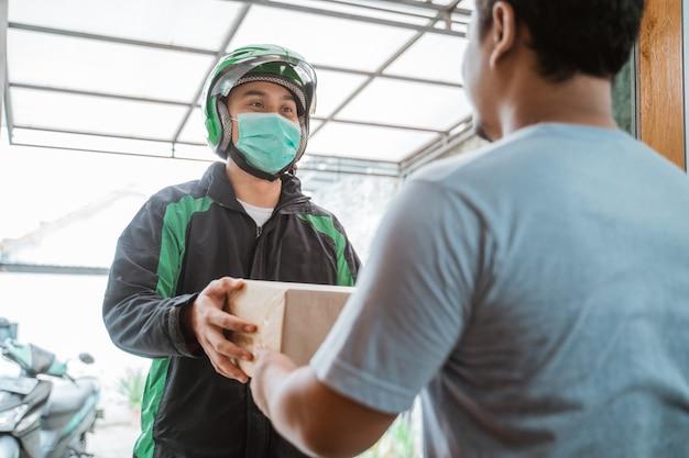 Correio entrega usando máscara facial ao entregar o pacote Foto Premium