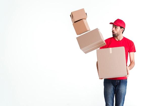 Correio homem deixa cair as caixas de encomendas e olhando com medo Foto gratuita