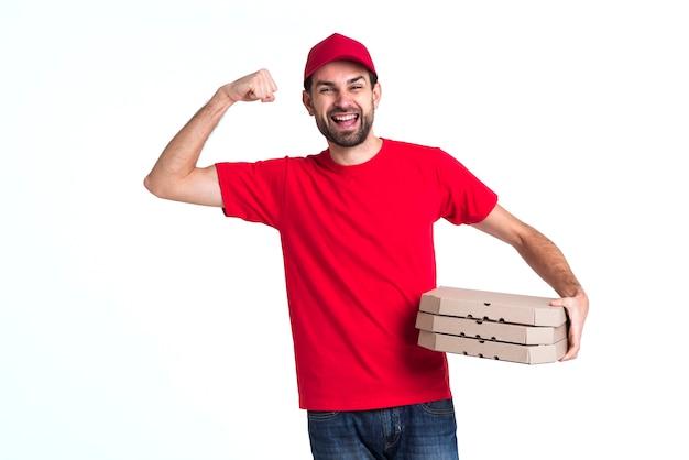 Correio homem segurando a pilha de caixas de pizza e mostrando os músculos Foto gratuita