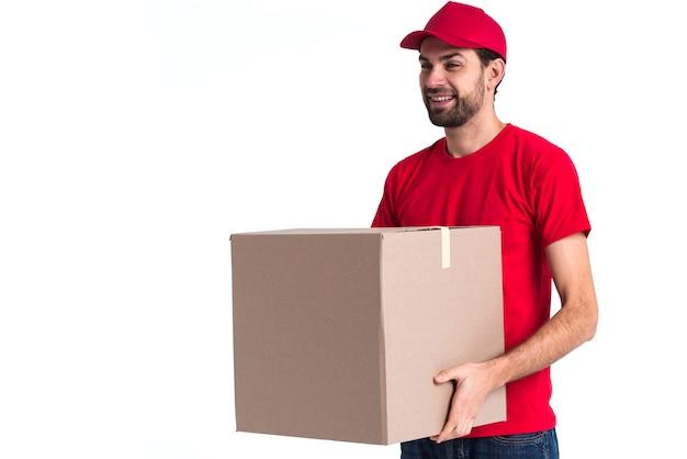 Correio homem segurando uma grande caixa de entrega Foto gratuita