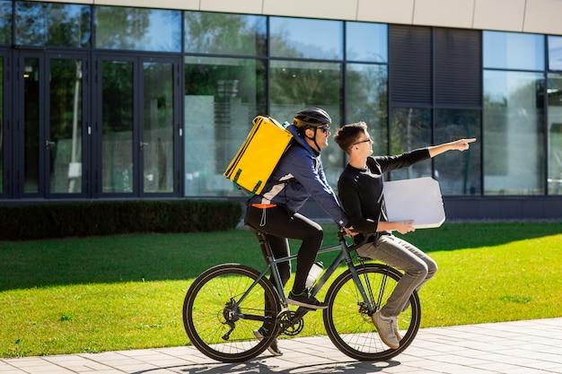 Correio masculino com bolsa térmica está carregando um cara com uma caixa no porta-malas de uma bicicleta. Foto Premium