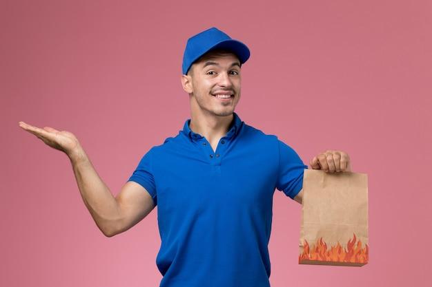 Correio masculino de uniforme azul segurando um pacote de comida de papel sorrindo na parede rosa, entrega de serviço de uniforme de trabalhador de vista frontal Foto gratuita