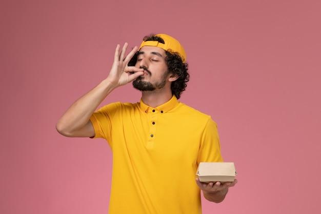 Correio masculino de vista frontal em uniforme amarelo e capa com pouco pacote de comida de entrega nas mãos, posando no fundo rosa. Foto gratuita