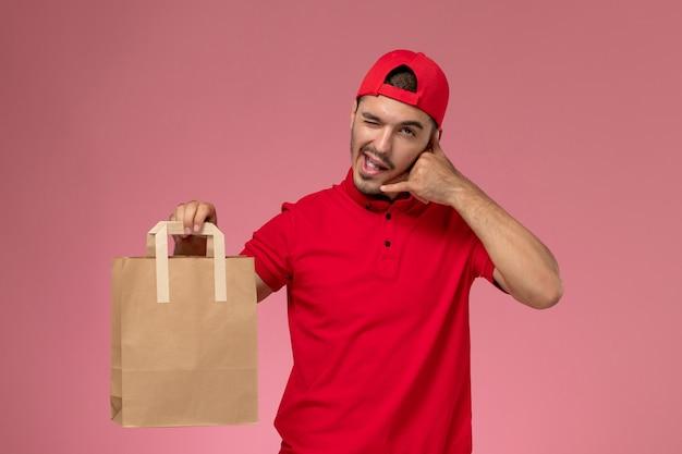 Correio masculino jovem de vista frontal na capa uniforme vermelha, segurando o pacote de comida de papel no fundo rosa claro. Foto gratuita