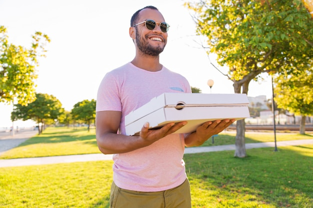 Correio masculino latino feliz carregando pizza no parque Foto gratuita
