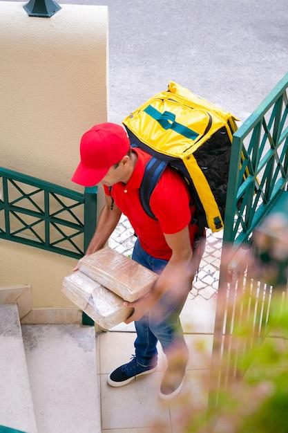 Correio profissional a entregar encomendas em casa e a trabalhar no serviço expresso. entregador caucasiano vestindo boné vermelho e camisa, carregando caixas e mochila amarela. serviço de entrega e pós-conceito Foto gratuita