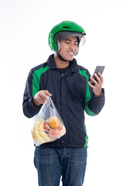Correio usando capacete e jaqueta uniforme segurando comida isolada Foto Premium