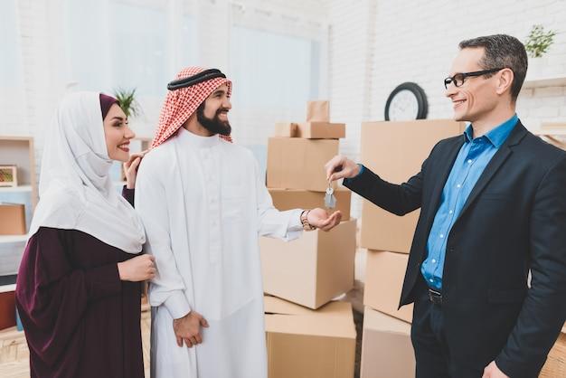 Corretor de imóveis dá chaves de casa família árabe feliz se move Foto Premium