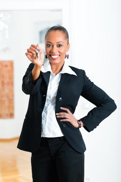 Corretor de imóveis jovem com chaves em um apartamento Foto Premium