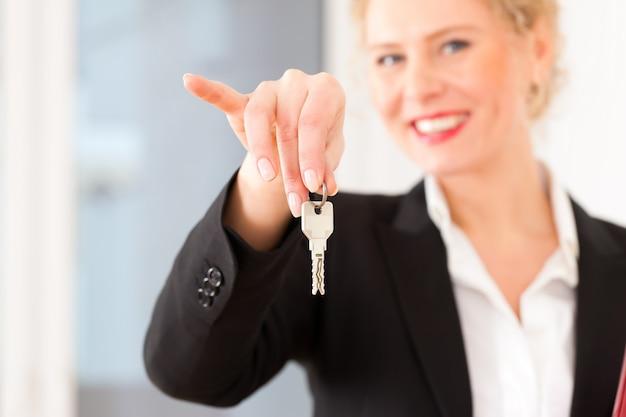 Corretor de imóveis jovem é com chaves em um apartamento Foto Premium