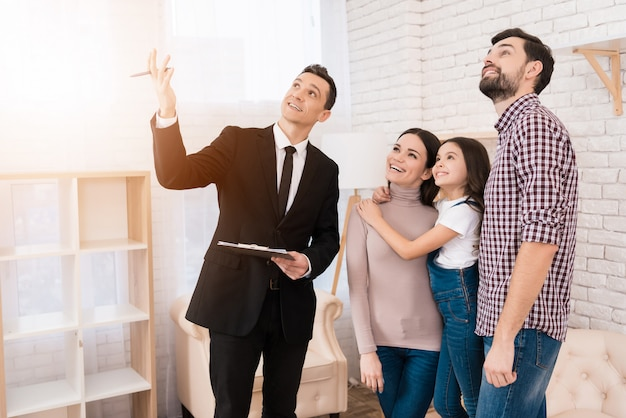 Corretor de imóveis no terno mostra casa de família que eles compraram. Foto Premium