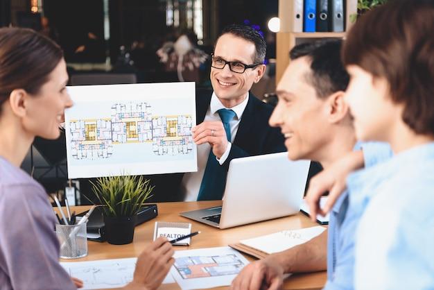 Corretor de imóveis sentado na mesa e mostrando o layout do apartamento. Foto Premium
