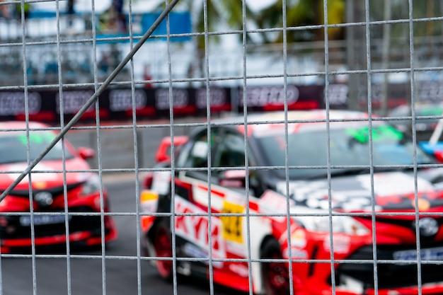 Corridas de carros do motorsport na estrada asfaltada. vista da rede da malha da cerca no carro borrado no fundo da pista. Foto Premium