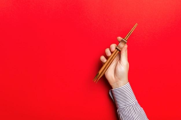 Cortada a imagem da mão masculina segurando os pauzinhos Foto Premium