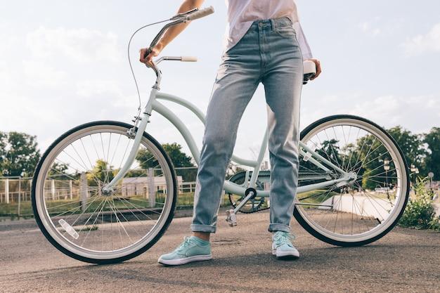 Cortada a imagem de uma mulher de jeans com uma bicicleta no parque Foto Premium