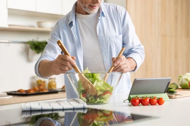 Cortada a imagem do homem maduro, cozinhar salada usando tablet Foto gratuita
