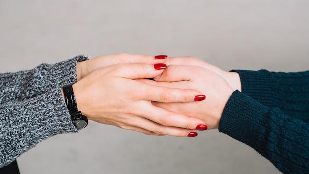 Cortada a imagem do psicólogo feminino segurando as mãos do seu cliente contra o pano de fundo cinzento Foto gratuita