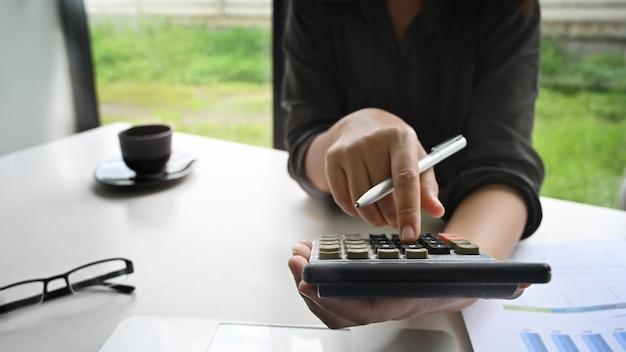 Cortada tiro mulher cálculo finanças dados na tabela. Foto Premium