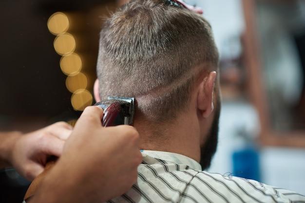 Cortado em close up de um homem recebendo seu cabelo estilizado por um barbeiro profissional na barbearia. Foto gratuita