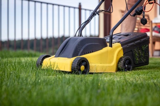 Cortador de grama no jardim Foto Premium