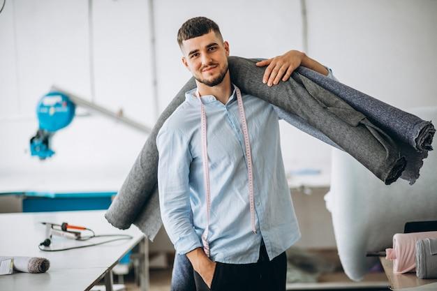 Cortador de homem em uma fábrica de costura, segurando o tecido Foto gratuita