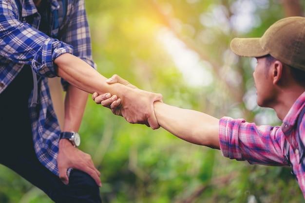 Cortar a imagem da mão do homem, ajudando um amigo a subir até o topo da montanha. Foto Premium