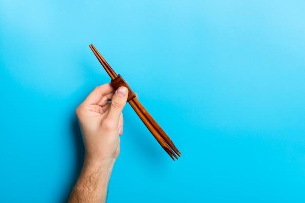 Cortar a imagem da mão masculina segurando os pauzinhos Foto Premium