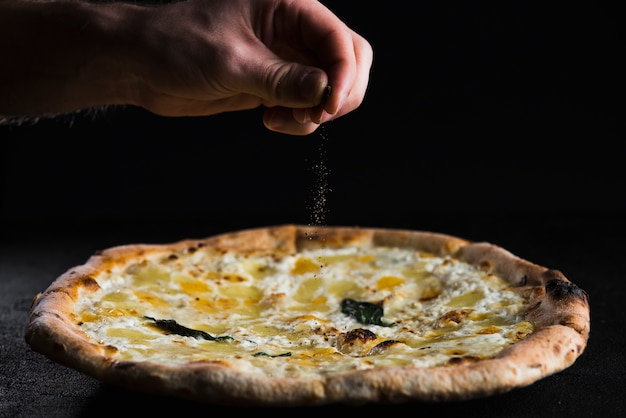 Cortar a mão espalhando especiarias na pizza Foto gratuita