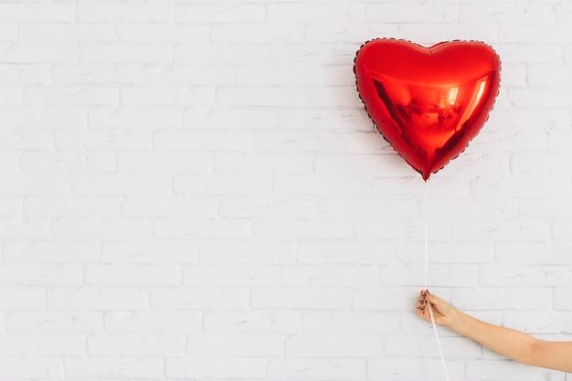 Cortar a mão segurando o balão do coração Foto gratuita