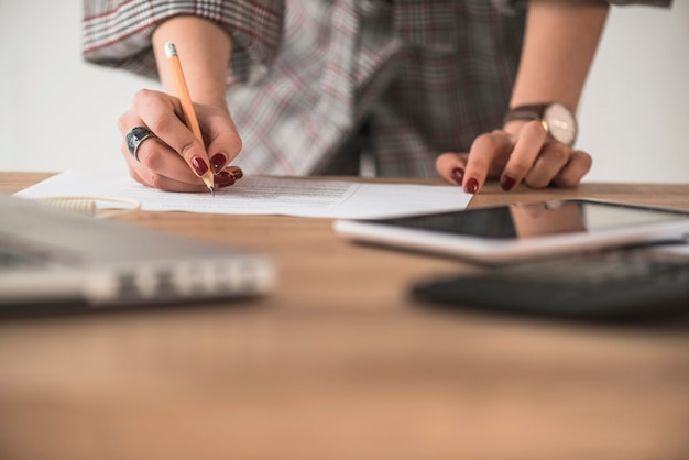 Cortar a mulher escrevendo no papel Foto gratuita