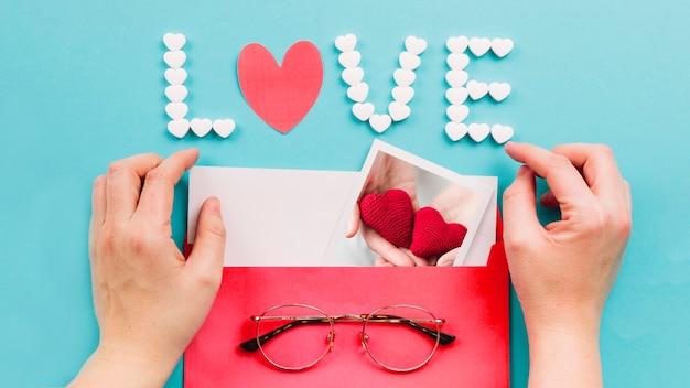 Cortar as mãos abrindo o envelope perto da escrita do amor Foto gratuita