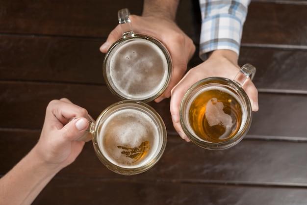 Cortar as mãos com bebida sobre a mesa Foto gratuita