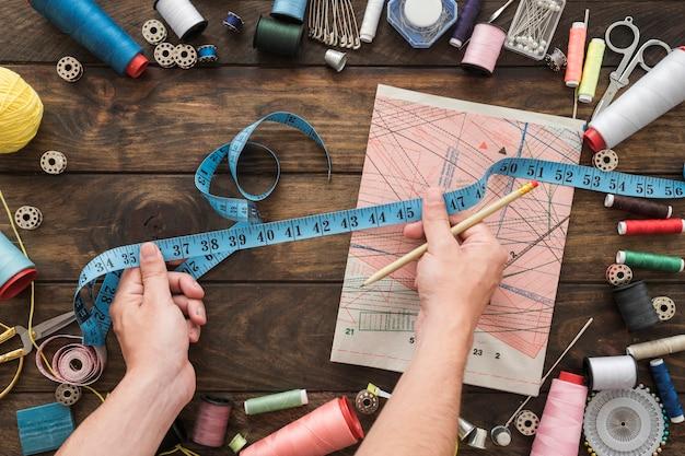 Cortar as mãos com fita métrica perto de material de costura Foto gratuita