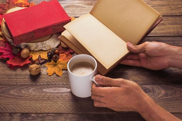 Cortar as mãos com livro e café perto de folhas e nozes Foto gratuita